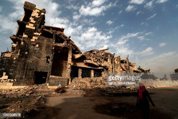 Woman walks past a damaged building in the Syrian city of Raqa on October 13, 2018.