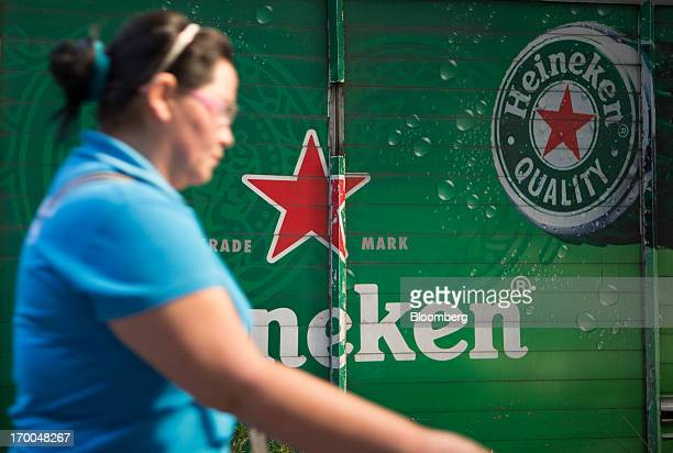 A woman walks past a delivery truck operated by CuauhtemocMoctezuma a subsidiary of Heineken NV in Mexico City Mexico on Thursday June 6 2013...