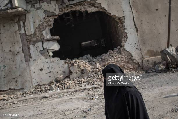 A woman walks past a destroyed building in an outer neighborhood of the Old City in West Mosul on November 6 2017 in Mosul Iraq Five months after...
