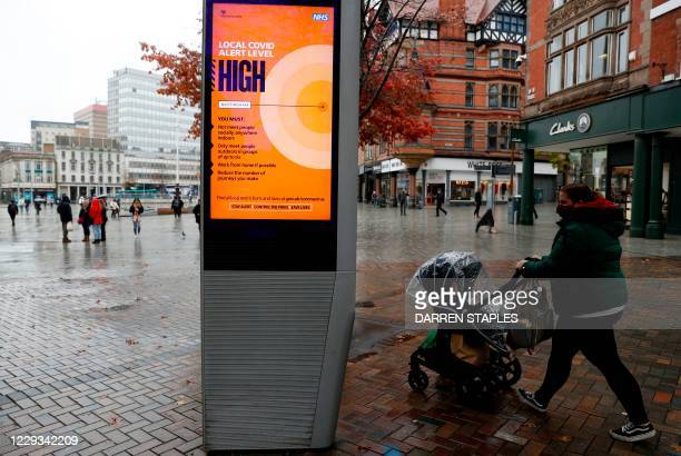 Woman walks past a digital display in Nottingham, central England warning pedestrians that the County is moving into coronavirus Tier 3 restrictions...