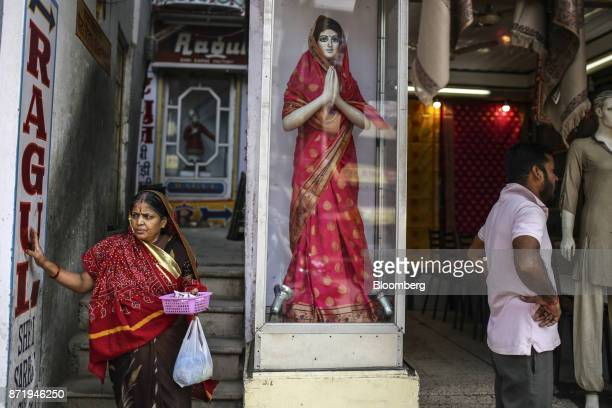 A woman walks past a display of a mannequin wearing a silk saree outside a store in Varanasi Uttar Pradesh India on Saturday Oct 28 2017 In Varanasi...