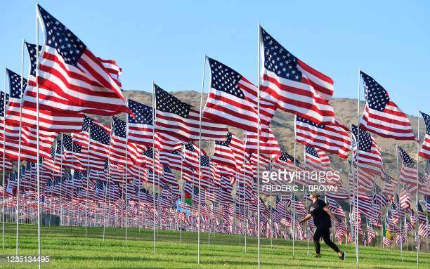 Woman walks past a display of US flags to commemorate the 20th anniversary of 9/11 with the annual Waves of Flags display and remembrance at...