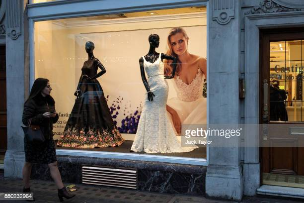 A woman walks past a dress shop with a bridal dress on display in Kensington on November 24 2017 in London England The American actress Meghan Markle...