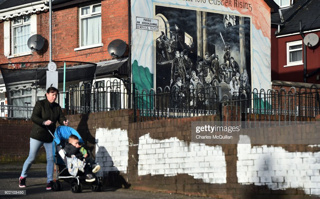 A woman walks past a dual Irish-English language street sign on February 21, 2018 in Belfast, Northern Ireland. Talks to restore the Northern Ireland power sharing executive collapsed last week with the main sticking point being a proposed Irish language act. A leaked draft agreement between Sinn Fein and the DUP confirmed a three-stranded approach to the language question, which would have resulted in an Irish language act, an Ulster-Scots act and a so-called respecting language and diversity act. The province has been without a government for over 13 months since then deputy First Minister Martin McGuinness resigned his position in protest at a botched renewable heating scheme.