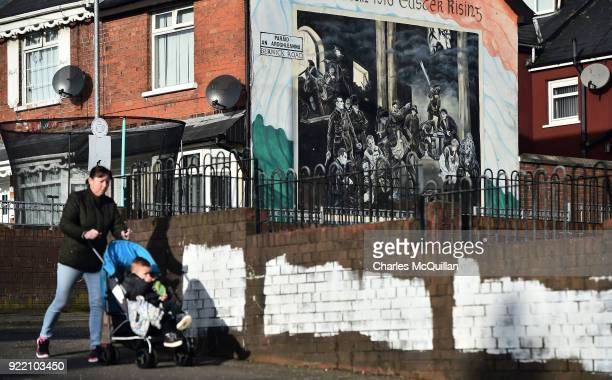 A woman walks past a dual IrishEnglish language street sign on February 21 2018 in Belfast Northern Ireland Talks to restore the Northern Ireland...