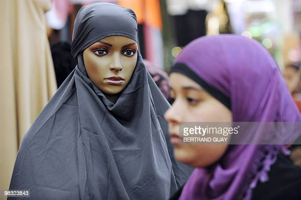Woman walks past a dummy covered with a veil at a stand during the annual meeting of French Muslims organized by the Union of Islamic Organisations...
