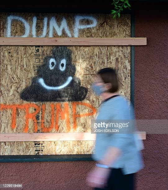 A woman walks past a Dump Trump sign on a boarded up window as people dance in the street to celebrate Joe Biden being elected President of the...