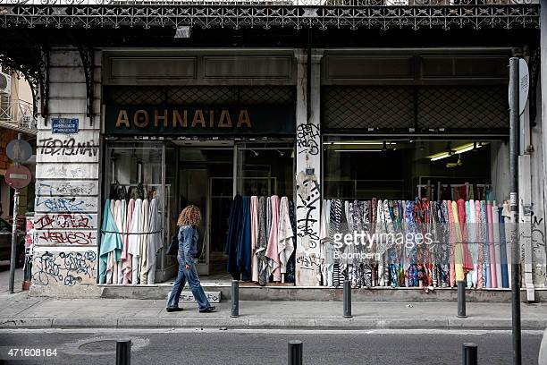 A woman walks past a fabric store in the Agia Irini district of Athens Greece on Saturday April 25 2015 The downturn that decimated the garment...
