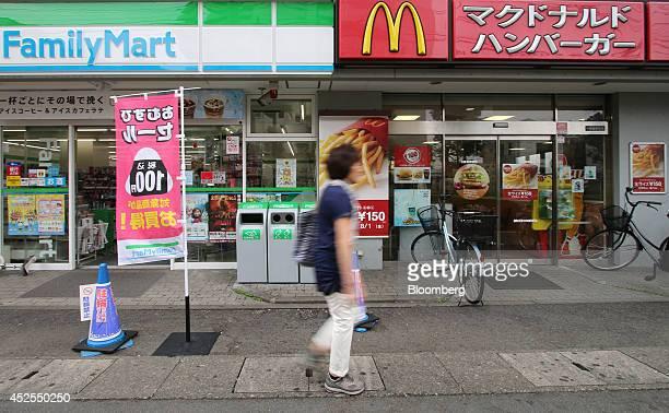 A woman walks past a FamilyMart Co convenience store and a McDonald's restaurant operated by McDonald's Holdings Co Japan Ltd in Kawasaki Kanagawa...