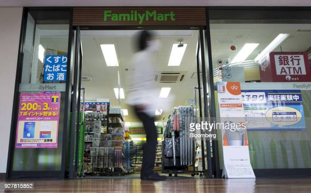 A woman walks past a FamilyMart UNY Holdings Co FamilyMart convenience store in Tokyo Japan on Friday Feb 23 2018 Conveniencestore chainsincluding...
