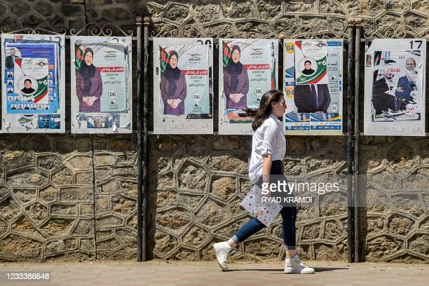 """Woman walks past a fence showing electoral posters of a candidate of the """"Future Front"""" political party in Algeria's capital Algiers on June 11 one..."""
