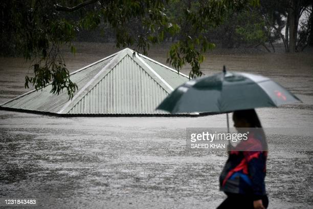 Woman walks past a flooded park along the overflowing Nepean river in Penrith suburb on March 21 as Sydney braced for its worst flooding in decades...