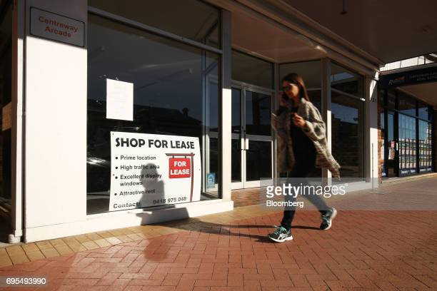 A woman walks past a 'For Lease' sign displayed in the window of a vacated commercial property in Narrabri Australia on Friday May 26 2017 A decade...