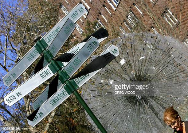 A woman walks past a fountain and signpost showing distances to some of the world's major cities 16 August 2005 in the popular Kings Cross tourist...