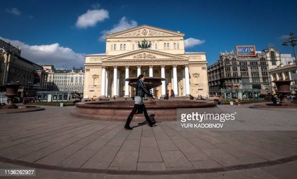 A woman walks past a fountain outside the Bolshoi Theatre in central Moscow on April 11 2019