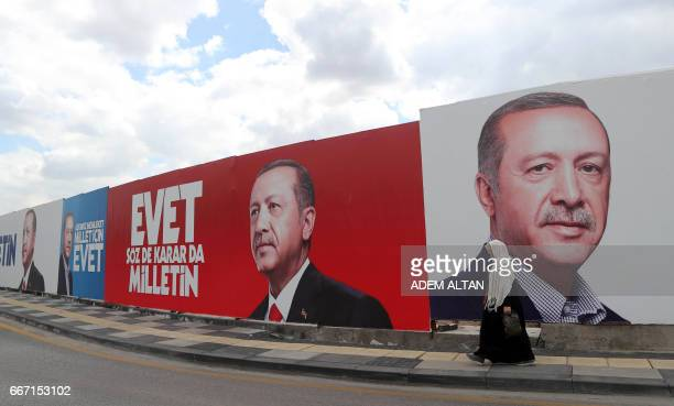 A woman walks past a giant poster bearing portraits of Turkish President Recep Tayyip Erdogan on April 11 2017 in Ankara ahead of the referendum on...