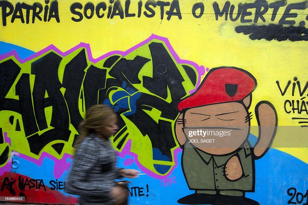 A woman walks past a graffiti mocking Venezuela's late president Hugo Chavez on March 26, 2013 in Paris.