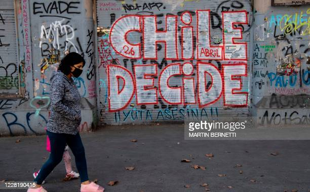 """Woman walks past a graffiti reading """"Chile Decides"""" in reference to the October 25 referendum to change Chile's military dictatorship era..."""