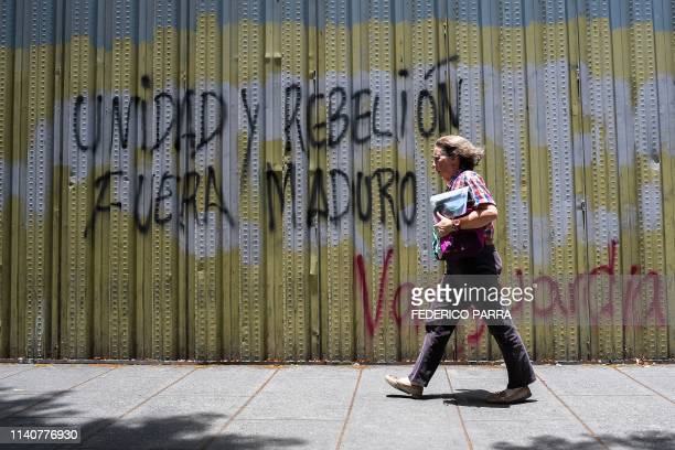 TOPSHOT A woman walks past a graffiti reading Unity and rebellion out Maduro in Caracas on May 2 2019 Two more opposition demonstrators both minors...