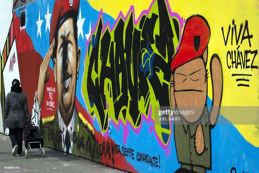 A woman walks past a graffiti representing Venezuela's late president Hugo Chavez on March 26, 2013 in Paris.