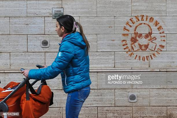 IDE A woman walks past a graffity reading 'Attention polluted city' in the Tamburi district of Taranto on March 18 2015 The site in Taranto in the...