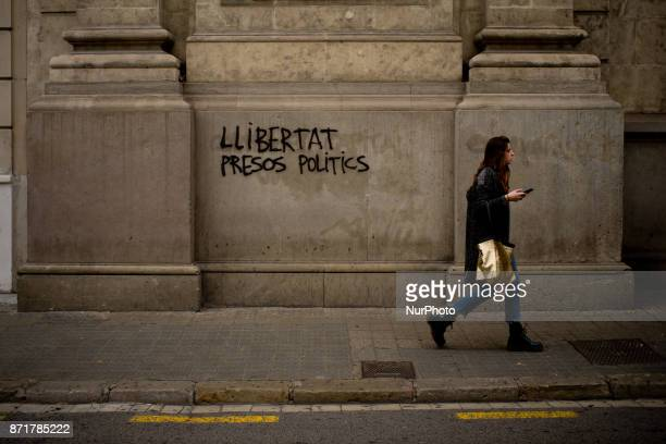 A woman walks past a grafiti reading 'freedom political prisioners' in Barcelona Spain on 8 November 2017 Catalonian territory went on general strike...