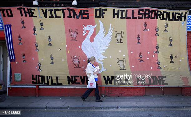 A woman walks past a Hillsborough tribute banner as fans arrive in Anfield for a memorial service marking the 25th anniversary of the Hillsborough...