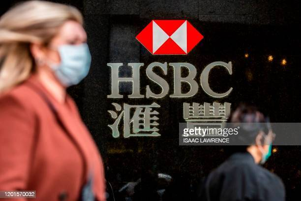 Woman walks past a HSBC sign in Hong Kong on February 18, 2020. - The London-based, Asia-focused behemoth HSBC is expected to release its Q4 and 2019...