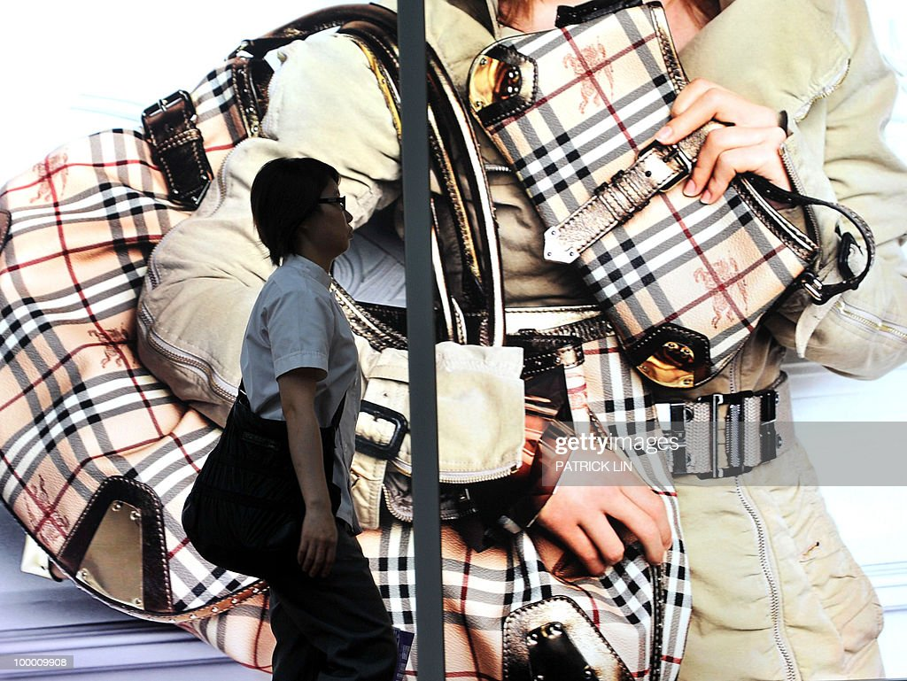 A woman walks past a huge commercial sign featuring luxury bags in Taipei on May 20, 2010. Taiwan said the economy grew at its fastest pace in more than 30 years during the first three months of 2010 due to strong demand for exports in markets such as China.