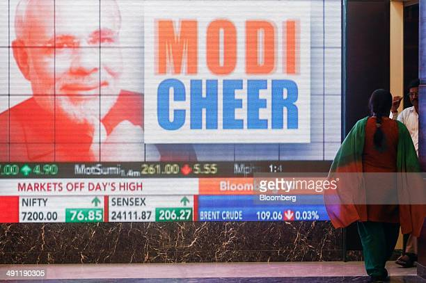A woman walks past a large screen showing television coverage of Narendra Modi prime ministerial candidate of the Bharatiya Janata Party during the...