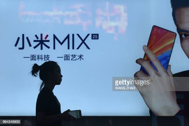 A woman walks past a light box advertisement of Xiaomi in Beijing on July 9 2018 Shares of Chinese smartphone giant Xiaomi fell almost 6 percent in...