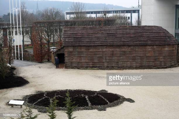 A woman walks past a longhouse of an Iroquois displayed at the exhibiton 'Iroquois' at Bundeskunsthalle in Bonn Germany 21 March 2013 The exhibition...
