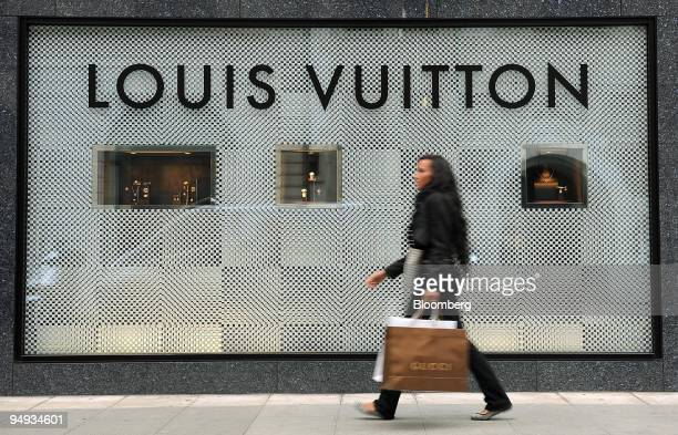 A woman walks past a Louis Vuitton store on Rue du Rhone in Geneva Switzerland on Friday Jan 30 2009 The Madoff affair came on top of the credit...