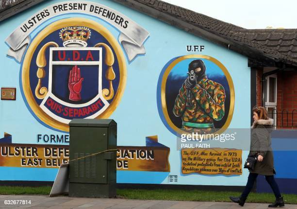 A woman walks past a loyalist mural depicting an Ulster Freedom Fighter on the Newtownards Road in Belfast on January 25 2017 Northern Ireland will...
