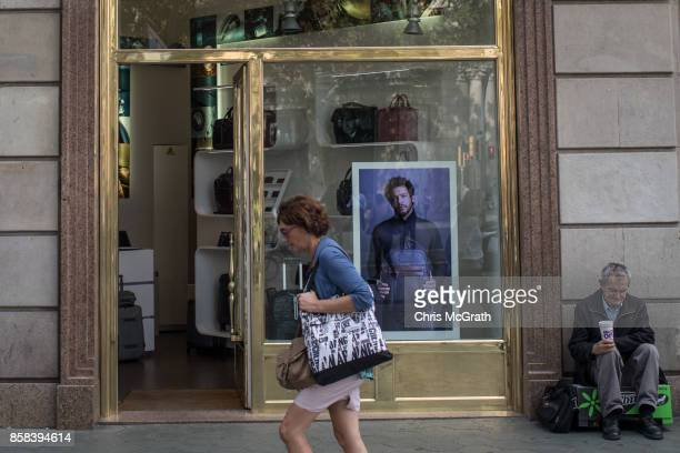 A woman walks past a luxury goods store as a man begs for money on October 6 2017 in Barcelona Spain Tension between the central government and the...