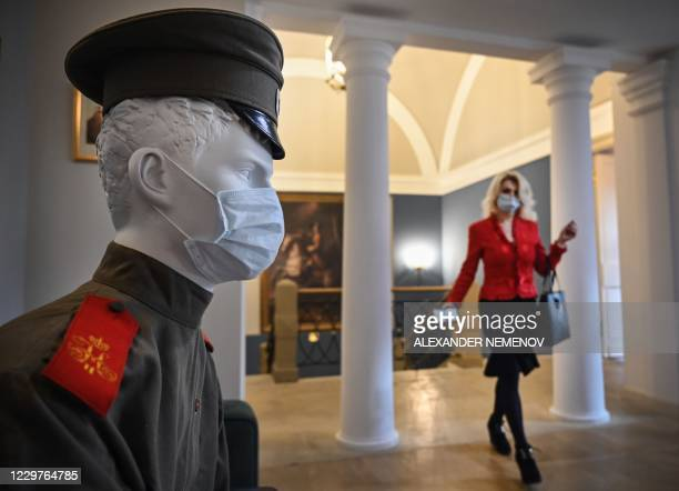 A woman walks past a mannequin wearing a WWI military uniform and a protective face mask in a Museum of Military Uniform in Moscow on November 24...