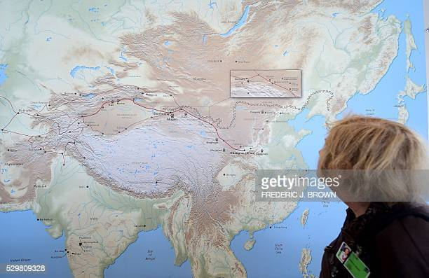 A woman walks past a map of China and Central Asia with red line signifying the ancient trade route known as thr Silk Road at the 'Cave Temples of...