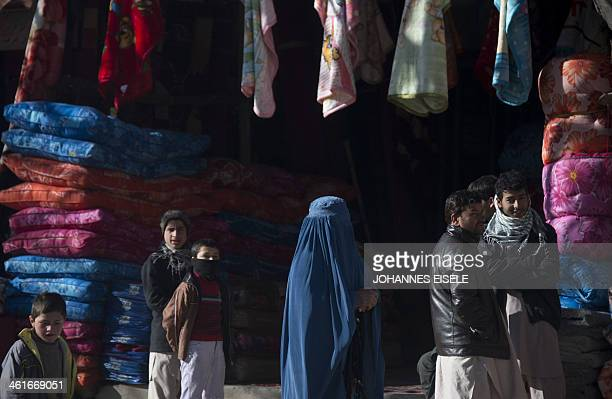 A woman walks past a mattress vendor in Kabul on January 10 2014 As winter sets in across Central Asia many Afghans struggle to provide adequate food...