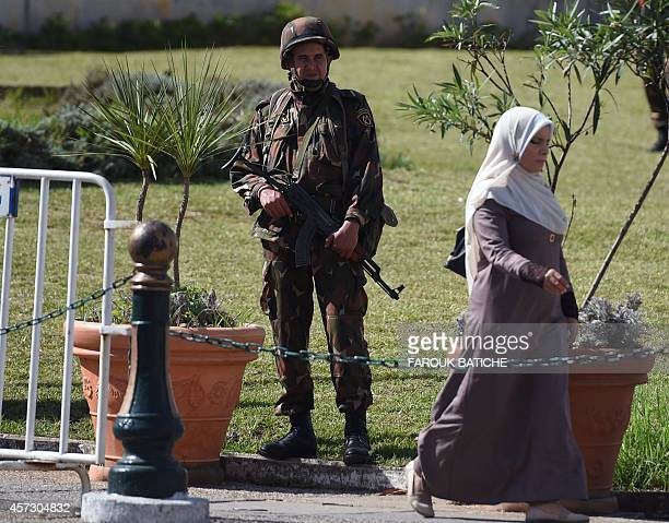 A woman walks past a member of the Algerian Republican Guard standing guard outside the presidential palace on October 16 2014 in the capital Algiers...