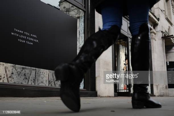 A woman walks past a message of tribute to late fashion designer Karl Lagerfeld at his store on Regent Street in London England on February 20 2019...