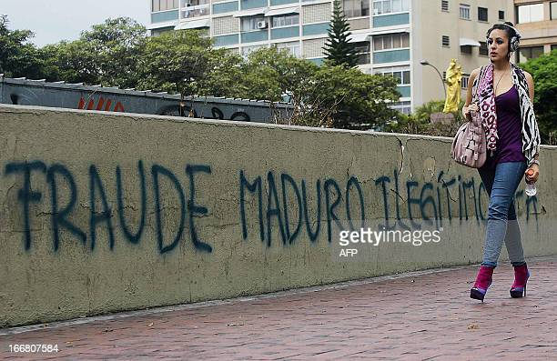 A woman walks past a message painted on a wall in the streets of Caracas reading 'Fraud Maduro Illegitimate' as a protest against Venezuelan...