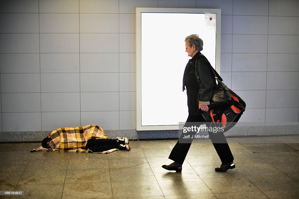 A woman walks past a migrant sleeping ,covered only in a blanket near Keleti railway station as they wait to board trains leaving for the Austrian border on September 14, 2015 in Budapest, Hungary. Migrants who arrive in Budapest overnight gather in the morning at the railway station as they try to be on the early trains leaving Budapest due to fears that the borders will possibly close in the coming days. Since the beginning of 2015 the number of migrants using the so-called 'Balkans route' has exploded with migrants arriving in Greece from Turkey and then travelling on through Macedonia and Serbia before entering the EU via Hungary. The number of people leaving their homes in war torn countries such as Syria, marks the largest migration of people since World War II.