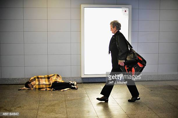 A woman walks past a migrant sleeping covered only in a blanket near Keleti railway station as they wait to board trains leaving for the Austrian...