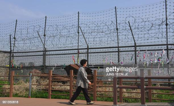 A woman walks past a military fence at Imjingak peace park in Paju near the demilitarized zone dividing the two Koreas on April 26 2018 ahead of the...