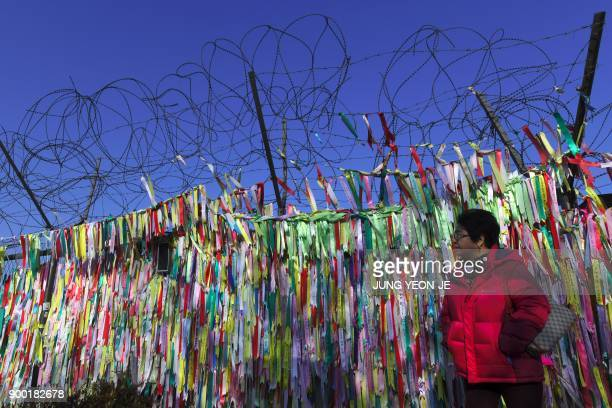 A woman walks past a military fence covered with ribbons calling for peace and reunification at the Imjingak peace park near the Demilitarized Zone...