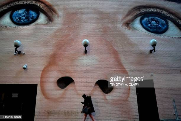 A woman walks past a mural by artist Jorge RodriguezGerada on the Westin Grand Central Hotel in midtown New York in New York January 10 2020 which is...