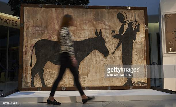 A woman walks past a mural by British artist Banksy's called 'Donkey Documents' which once adorned the wall of a private building in Bethlehem in the...
