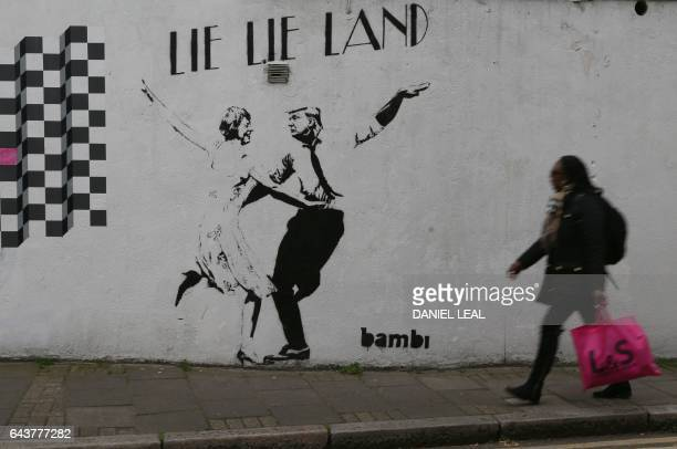A woman walks past a mural by English street artist Bambi depicting British Prime Minister Theresa May dancing with US President Donald Trump in...