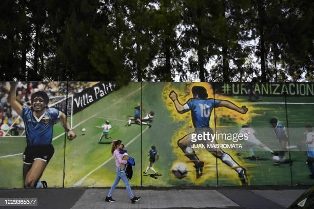 "Woman walks past a mural by street artist ""Uasen"" depicting Argentine former football star Diego Maradona -current coach of Gimnasia y Esgrima La..."