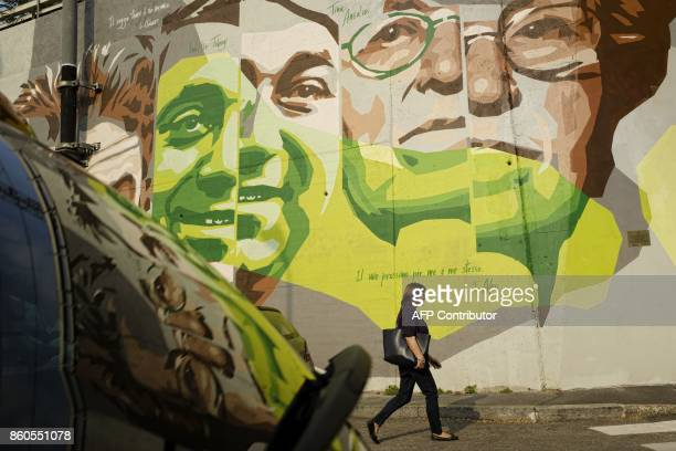 A woman walks past a mural depicting late Italian journalist and writer Walter Tobagi and late Italian politician Tina Anselmi on October 11 2017 in...